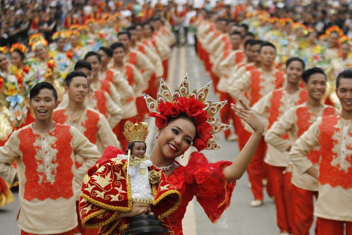 A Filipino woman in colourful costume holds a statue of the Santo Nino (Child Jesus) as she performs during the Sinulog Grand Parade marking the feast of Child Jesus in Cebu City, Philippines, on Jan 21, 2018.