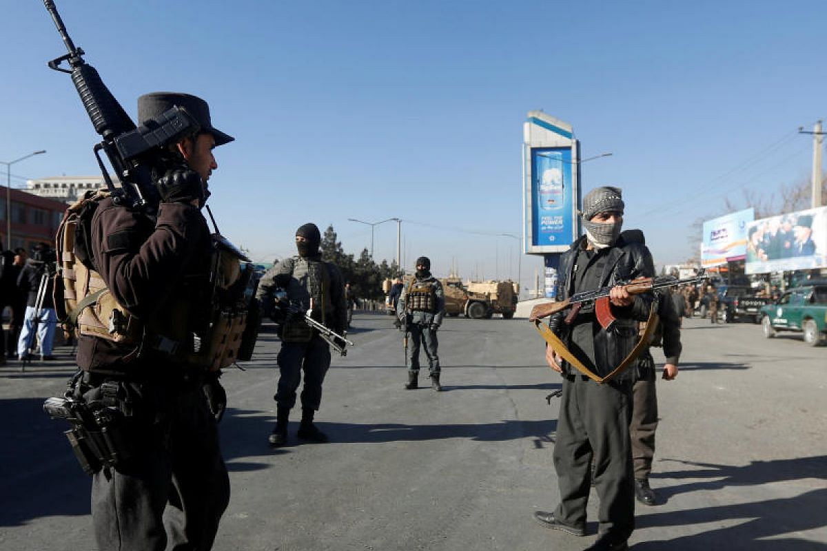 Afghan policemen keep watch close to the entrance gate of Kabul's Intercontinental Hotel during an attack by gunmen in Kabul, Afghanistan on Jan 21, 2018.