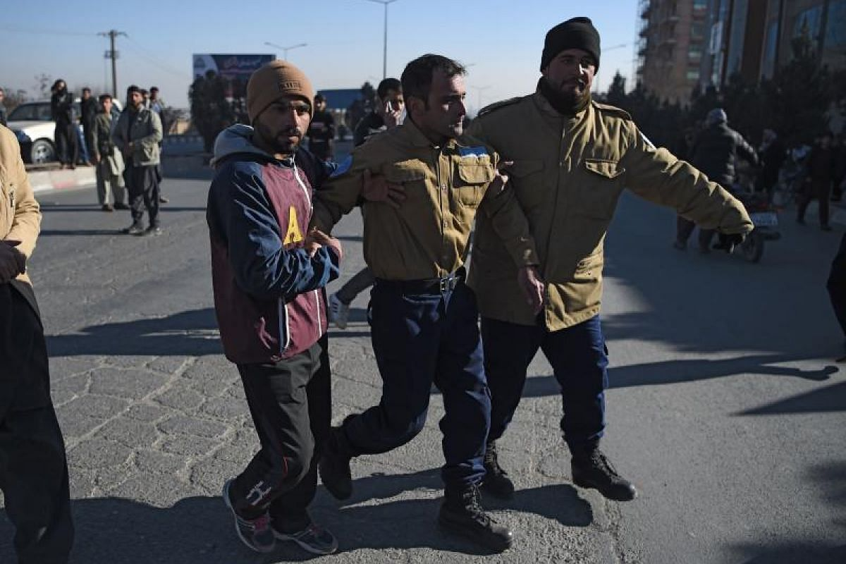 Afghan security from a private company assist an injured colleague near the Intercontinental Hotel following an attack by gunmen in Kabul on Jan 21, 2018.
