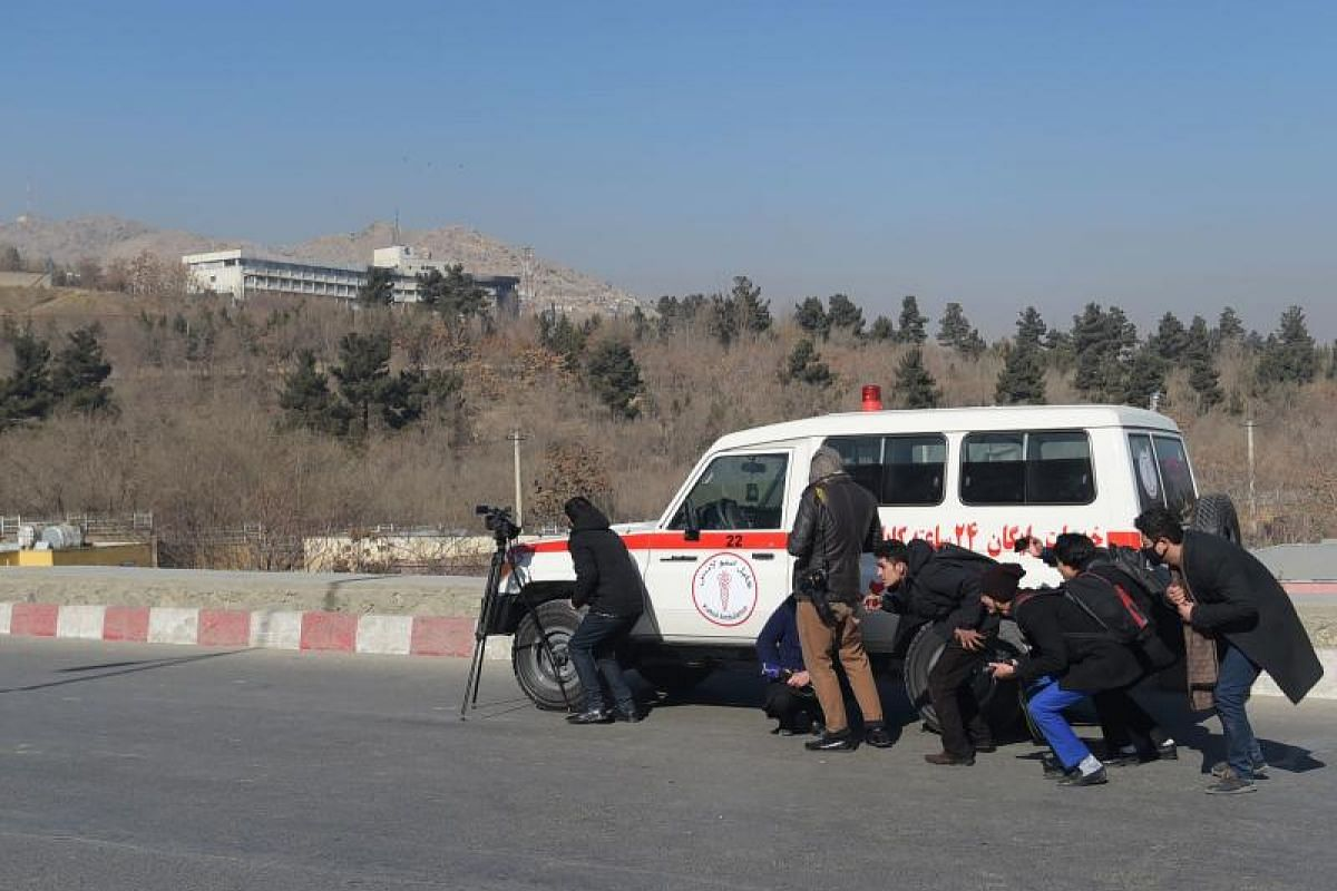 Afghan journalists take cover behind an ambulance near the Intercontinental Hotel during a fight between gunmen and Afghan security forces in Kabul on Jan 21, 2018.