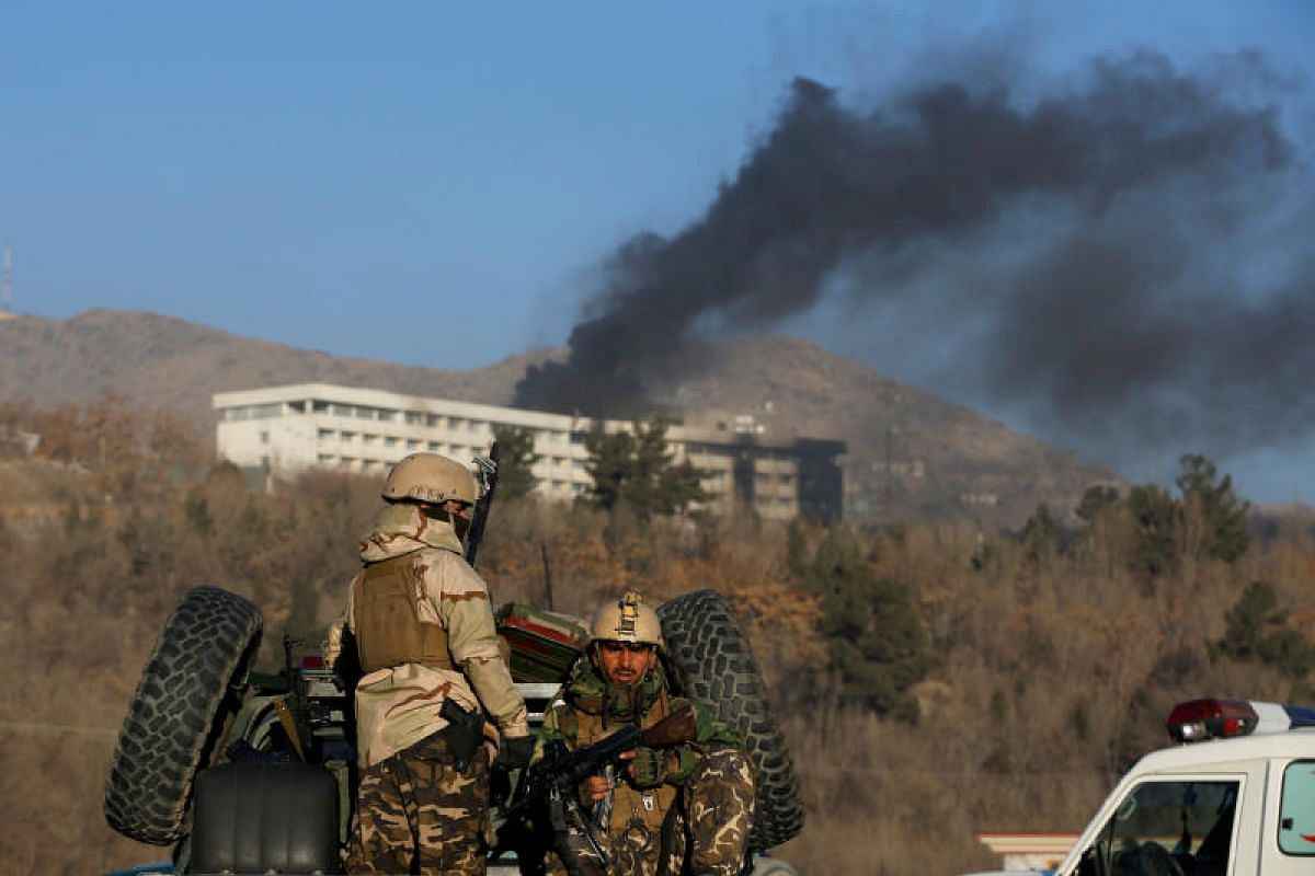 Afghan security forces keep watch as smoke rises from the Intercontinental Hotel in Kabul on Jan 21, 2018.