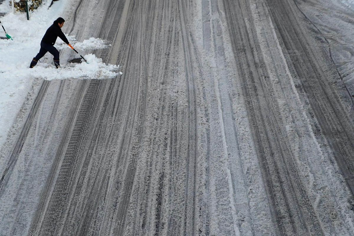 A man clears snow at a road in Tokyo, on Jan 23, 2018.