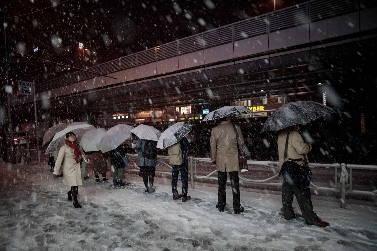 People wait in a queue for taxis at Akihabara station in Tokyo on Jan 22, 2018.