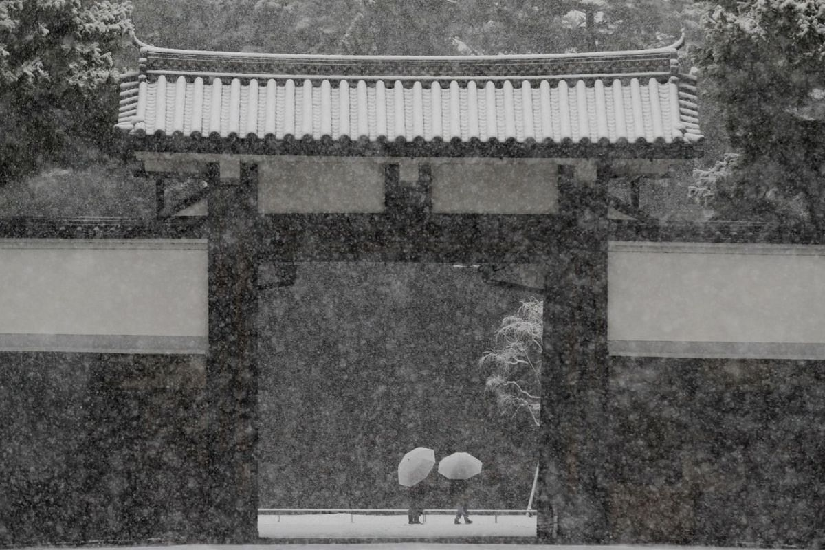 People holding umbrellas make their way in the heavy snow at the Imperial Palace in Tokyo, Japan on Jan 22, 2018.