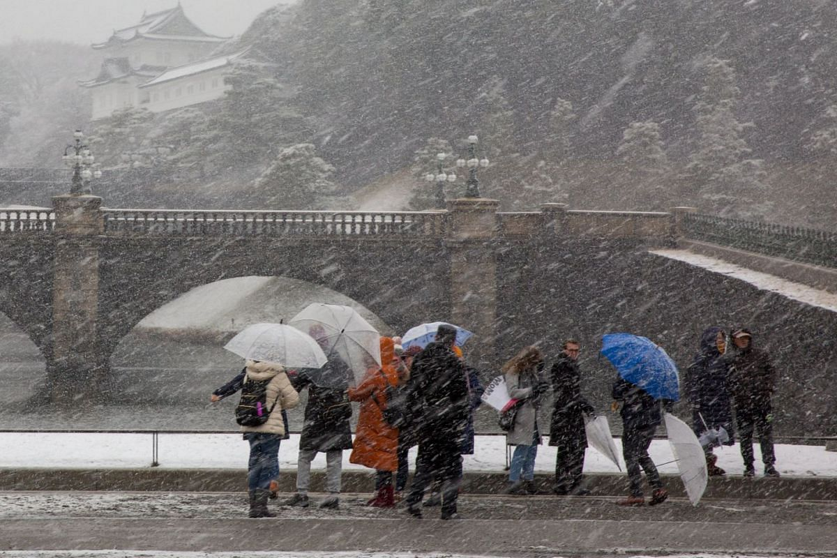 Visitors congregate as snow falls over the Imperial Palace in Tokyo, Japan, on Jan 22, 2018.