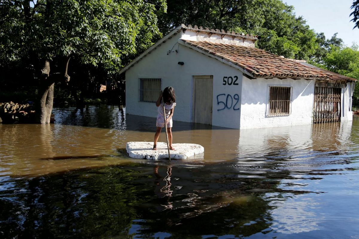 A young girl uses a piece of styrofoam as a paddle board next to a flooded home after heavy rains caused the river Paraguay to overflow, on the outskirts of Asuncion, Paraguay January 23, 2018.