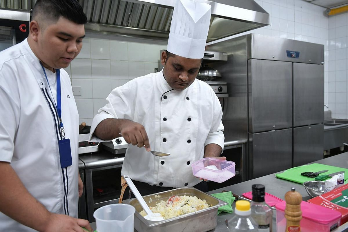 Mr Paul Simon preparing briyani rice for President Halimah Yacob as he is watched over by resident chef Muhammad Adi Rezza in the halal kitchen of the Istana, on Jan 24, 2018.