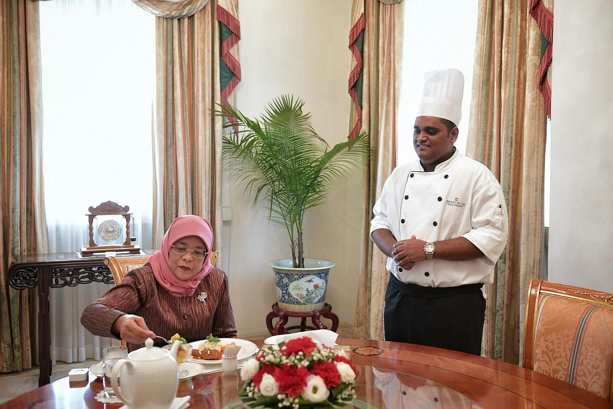 President Halimah Yacob reaching for the mango salsa salad as Mr Paul Simon looks on.