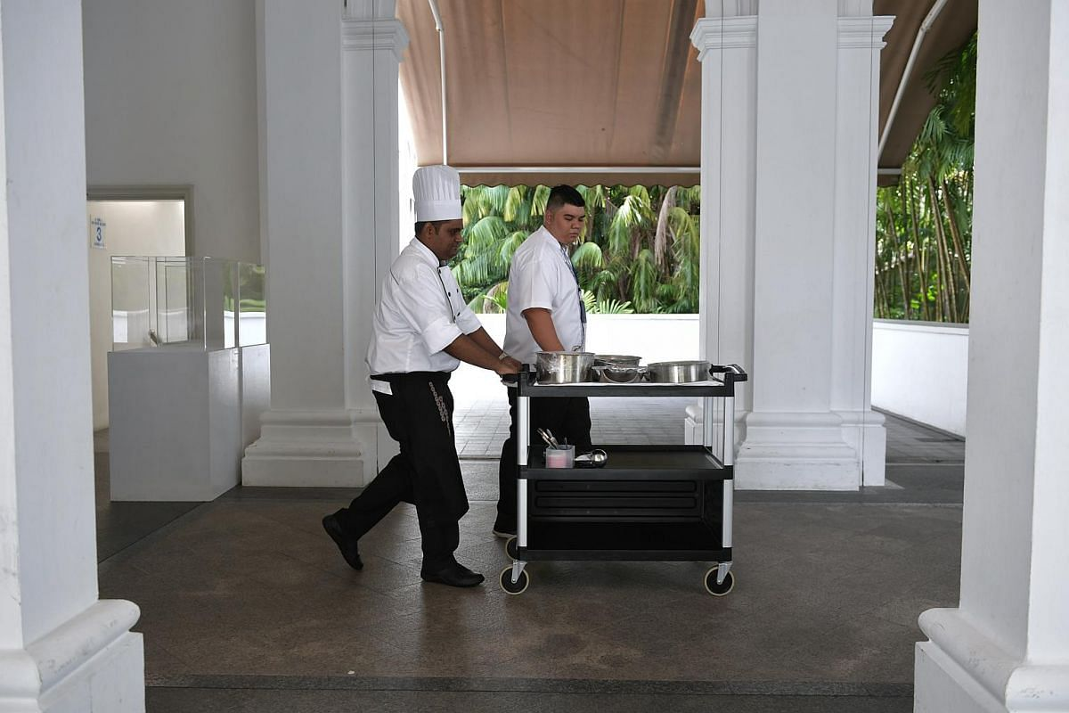 Mr Paul Simon taking the prepared food to the pantry on a trolley as he is followed by resident chef Muhammad Adi Rezza.
