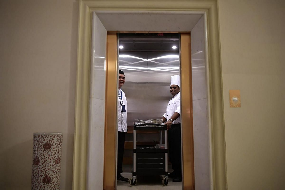 Mr Paul Simon and resident chef Muhammad Adi Rezza taking the lift to the pantry at the Istana, together with the trolley of prepared food.