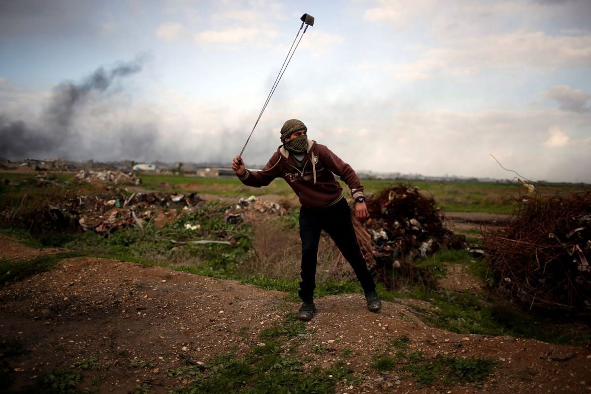 A Palestinian protester holds a sling at the scene of clashes with Israeli troops near the border with Israel, east of Gaza City, on Jan 19, 2018.