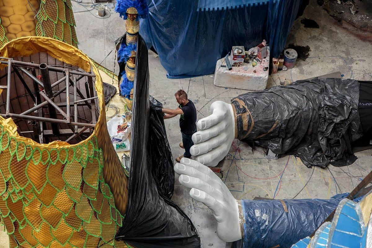 A worker stands next to parts of an allegorical car being prepared for a Carnival parade at a samba school studio in Sao Paulo, on Jan 12, 2018.