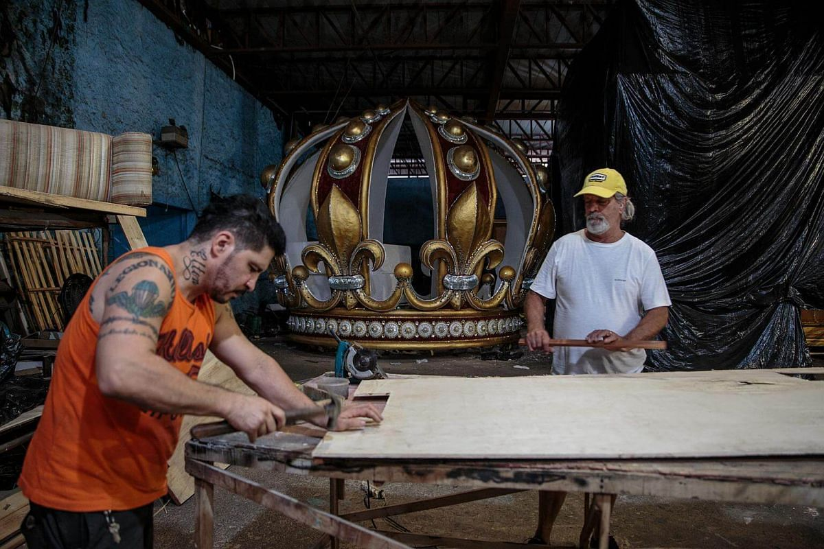A worker hammers wood while creating an allegorical car for a Carnival parade at a samba school studio in Sao Paulo, on Jan 12, 2018.