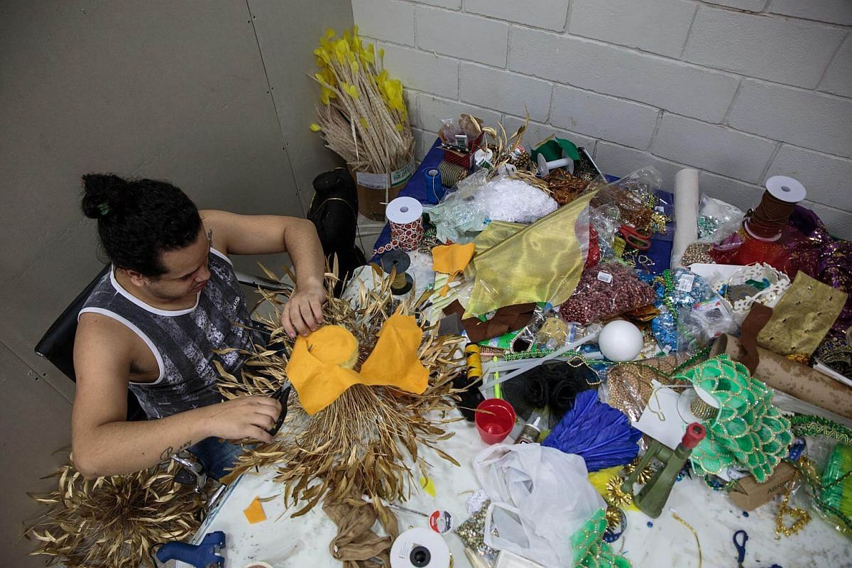 A worker cuts fabric while creating a costume for a Carnival parade at a samba school studio in Sao Paulo, on Jan 12, 2018.