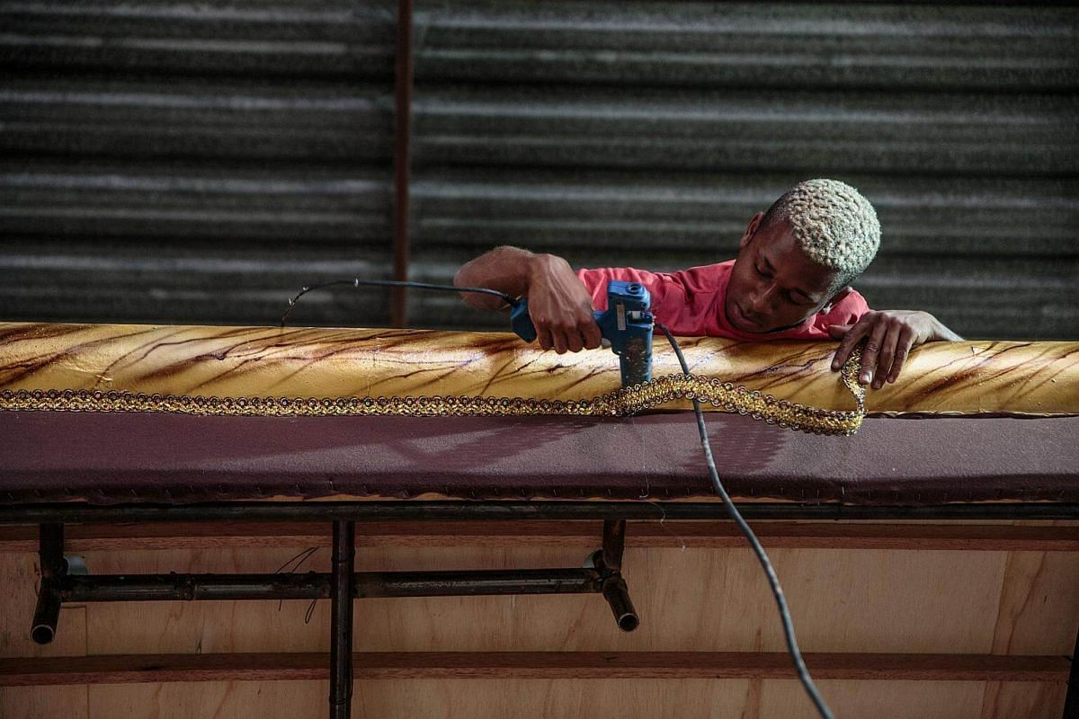 A worker hot glues trim an allegorical car under construction for a Carnival parade at a samba school studio in Sao Paulo, on Jan 12, 2018.