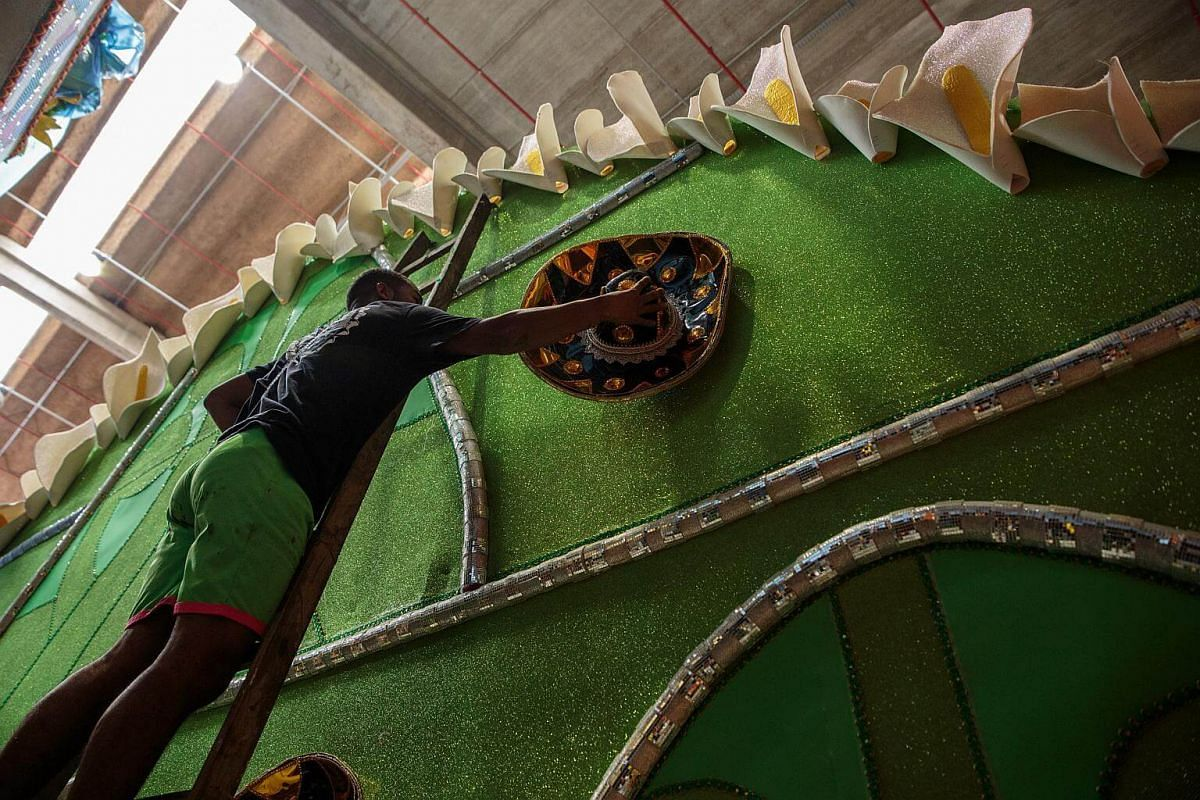 A worker puts decoration on an allegorical car for a Carnival parade at a samba school studio in Sao Paulo, on Jan 12, 2018.