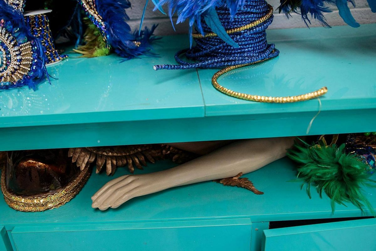 A mannequin lies between costume trim used to create costumes for Carnival at a samba school studioin Sao Paulo, on Jan 12, 2018.