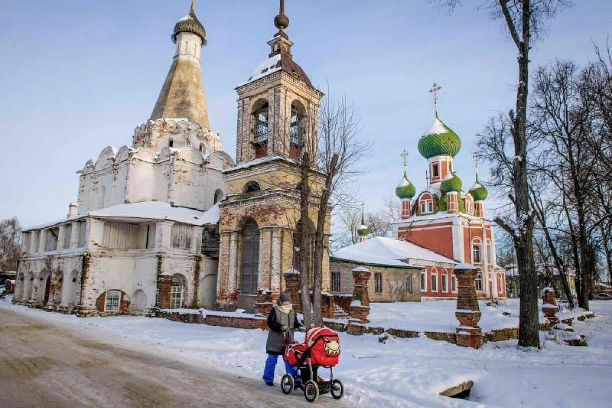 A woman pushes a pram in front of several Orthodox churches in the historical center of the town of Pereslavl-Zalessky on Jan 25, 2018. Pereslavl-Zalessky is part of the so called Golden Ring of Russia comprising several cities northeast of Moscow. P