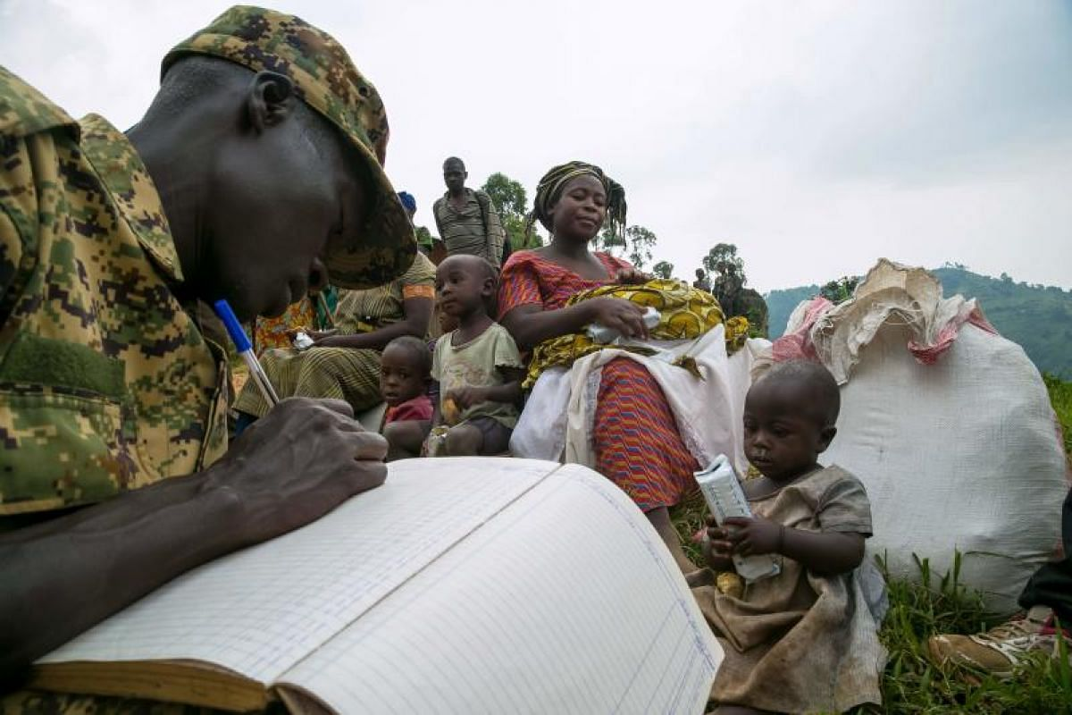 A Ugandan soldier registering some civilians after they crossed the border from the Democratic Republic of Congo to be refugees at Nteko village in western Uganda on Jan 24, 2018.