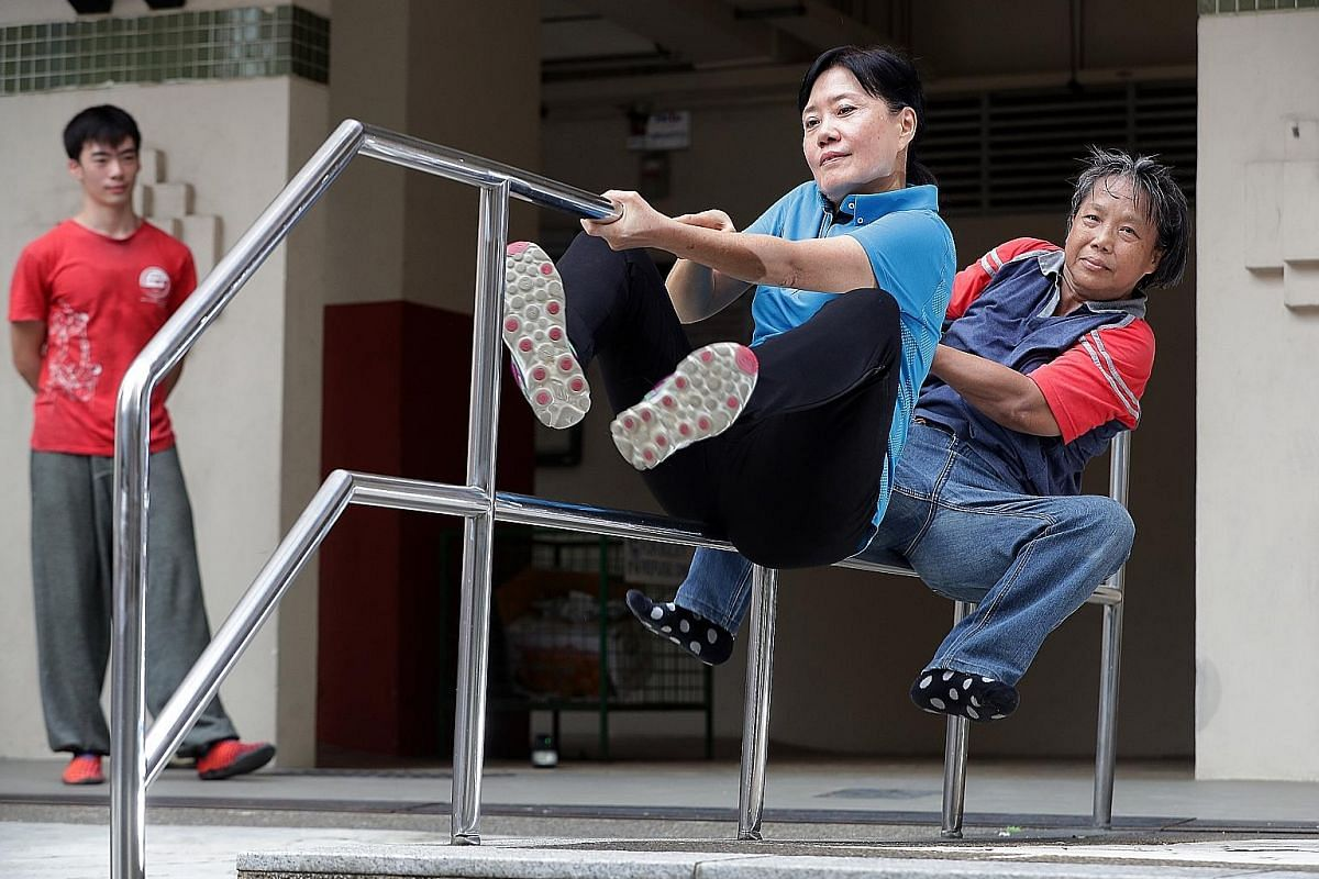 Move Academy Singapore coach Tan Shie Boon keeps a close watch on Madam Kimm Chai (left) and Ms Ann Tham as they execute a parkour move. Both women, who took up the sport last year, say that they have benefited from the training in terms of protectin