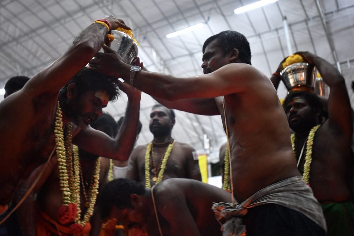 A devotee receiving his milkpot. Devotees seek blessings and fulfil their vows by carrying milk pots as offerings.