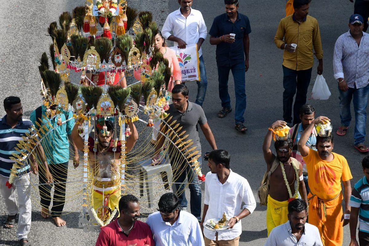 A devotee bearing a kavadi walking from Sri Srinivasa Perumal Temple to Sri Thendayuthapani Temple.