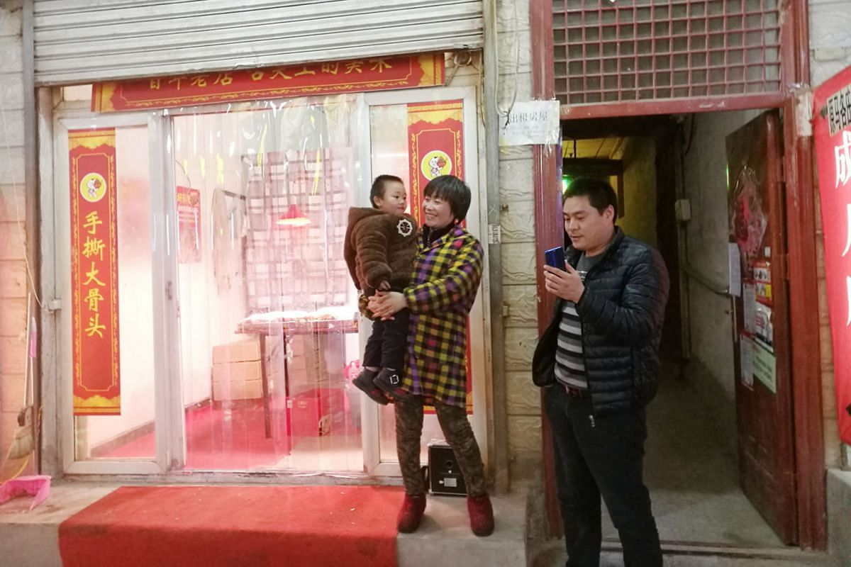 """The case of """"Snowflake Boy"""" Wang Fuman, whose story went viral in China - and worldwide - last month, focused attention on the plight of China's 61 million """"left-behind"""" children, whose parents work in faraway cities. A couple with their daughter in"""