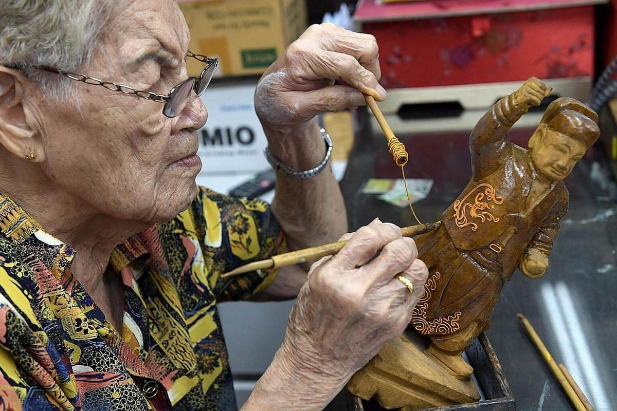 Keeping alive a vanishing art: The Say Tiang Hng Buddha Shop has been around for 122 years, and is Singapore's last remaining hand-made effigy shop. Madam Tan Chwee Lian, 87, who is seen here working on an effigy, runs the shop with one of her sons.