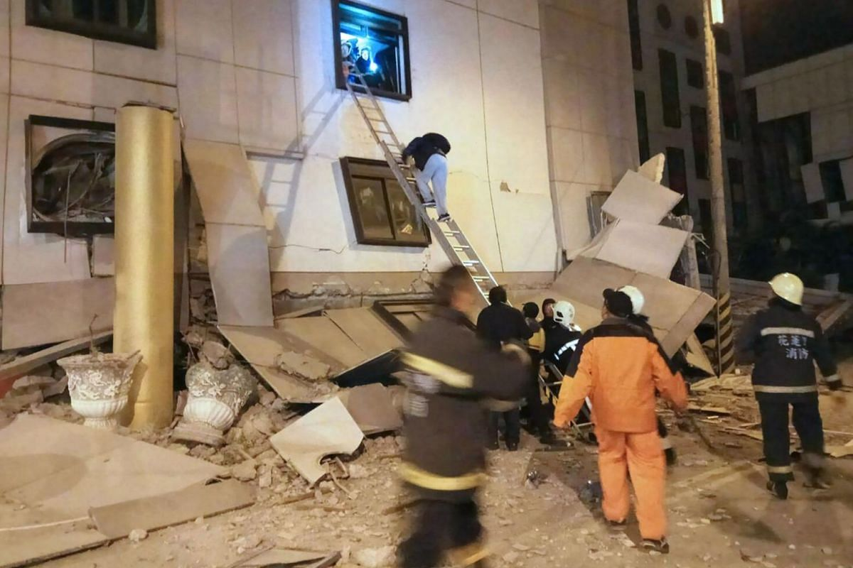 Rescue workers searching through rubble outside Marshal Hotel in Hualien.