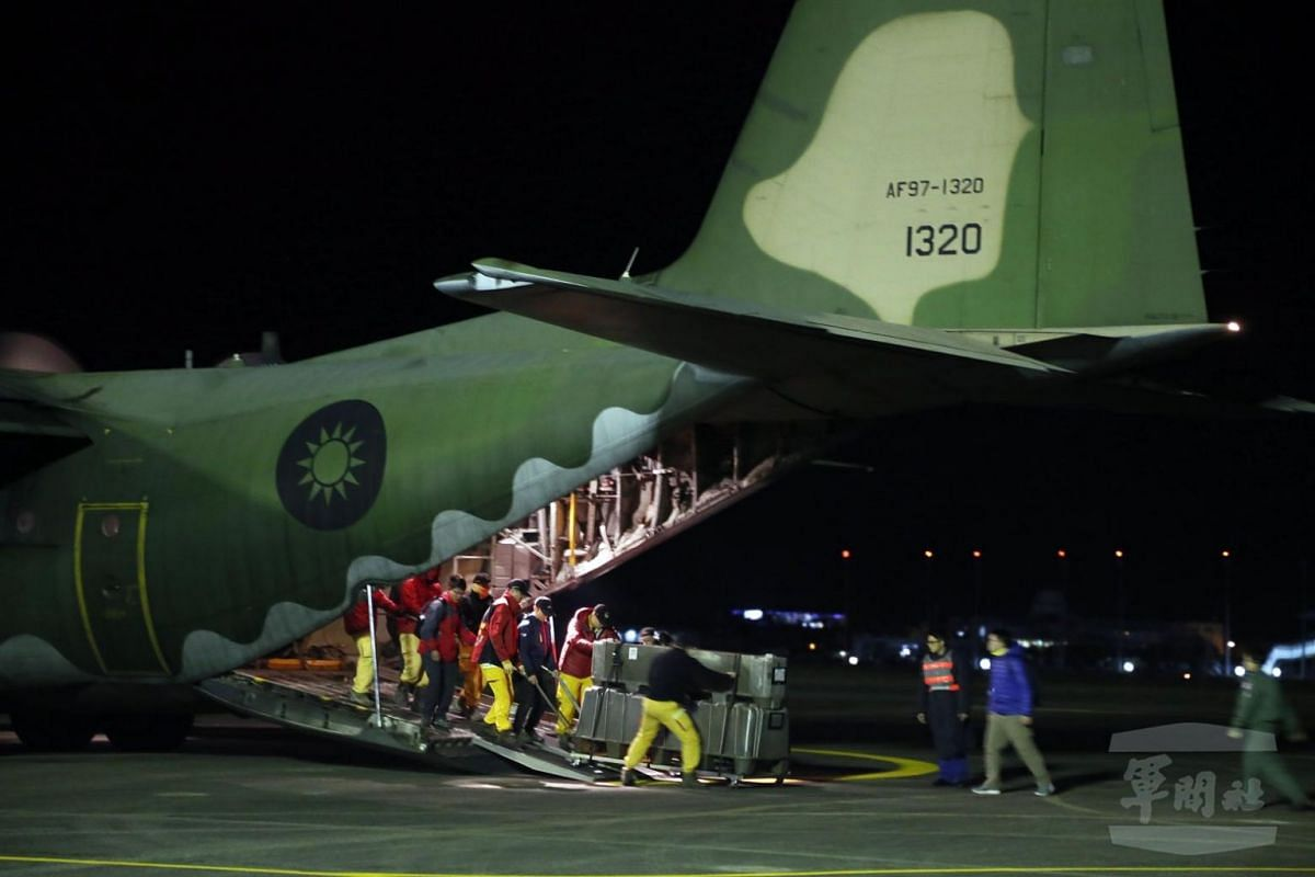 Military personnel loading a C-130 transport plane before taking off from the Taipei Songshan Airport to rush rescue personnel and relief goods to Hualien.