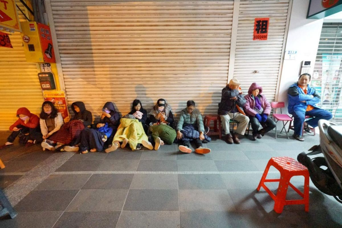Guests who had evacuated the damaged Marshal Hotel sit outside a building following the earthquake.