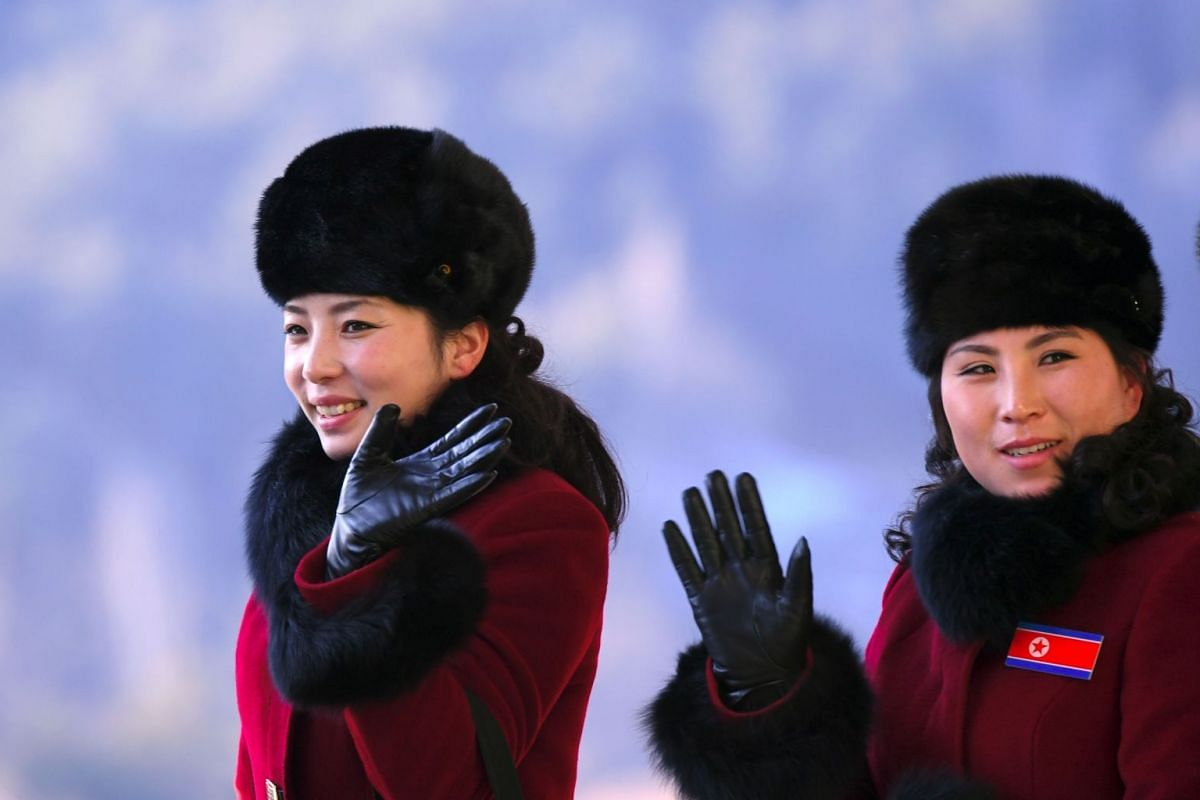 North Korean cheerleaders wave to the media as they walk to their accomodation at the Inje Speedium, on Feb 7, 2018.