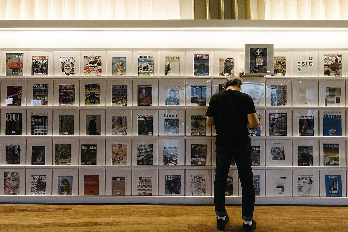 A reader at library@orchard at the magazine wall. Located at Orchardgateway, the library has a focus on design.