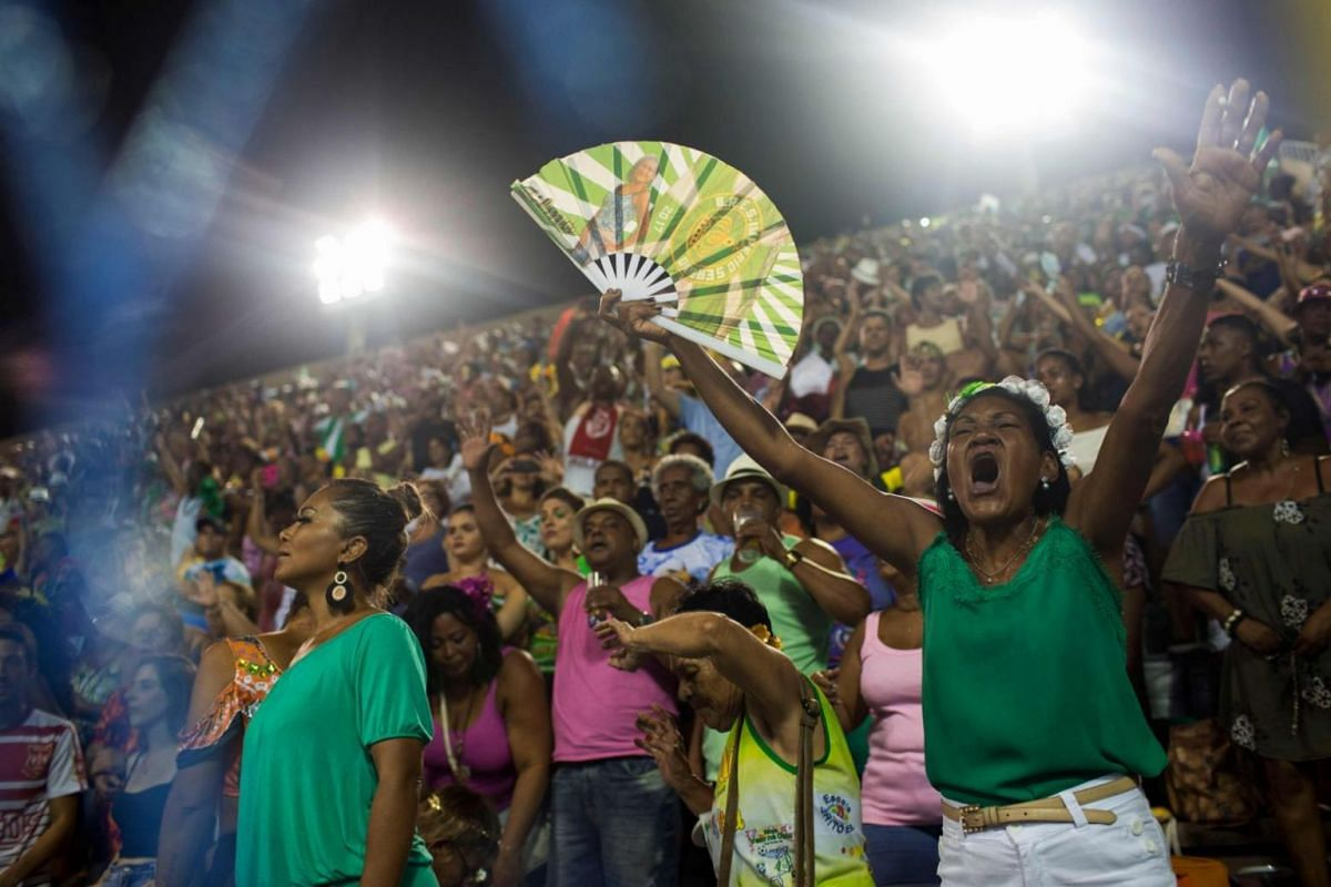 Spectators cheer as revellers of the Imperio Serrano perform on the first night of the Rio Carnival at the Sambadrome.