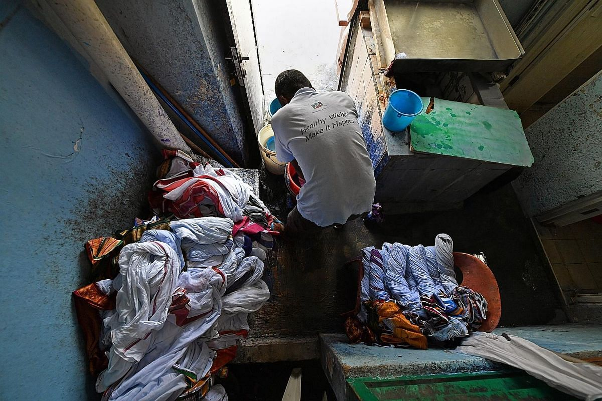 Mr Sambasivam unloading freshly washed laundry to be starched and dried later. The 73-year-old is a family friend who helps out in the shop, doing mainly administrative work. Left: After starching, the white dhotis are soaked in a pail of water with
