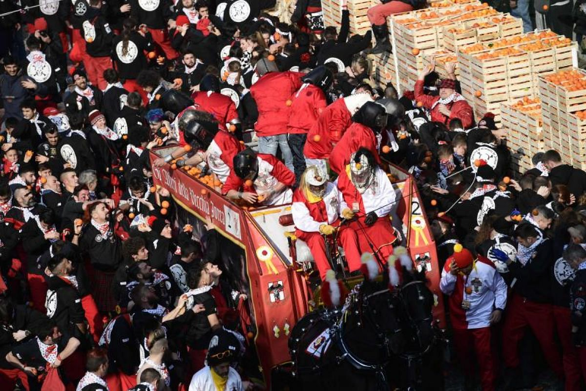 People throw oranges at each other during the traditional Ivrea Carnival on Feb 11, 2018.
