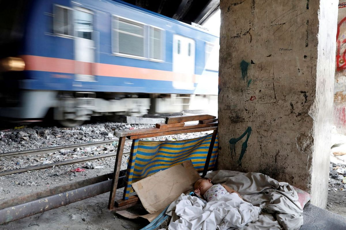 A baby sleeps in a cot while a train passes by in Santa Mesa district, Metro Manila, Philippines February 12, 2018. PHOTO: REUTERS