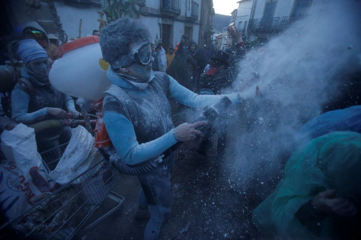 """Revellers participate in a flour fight during the """"O Entroido"""" festival in Laza village, Spain February 12, 2018. PHOTO: REUTERS"""