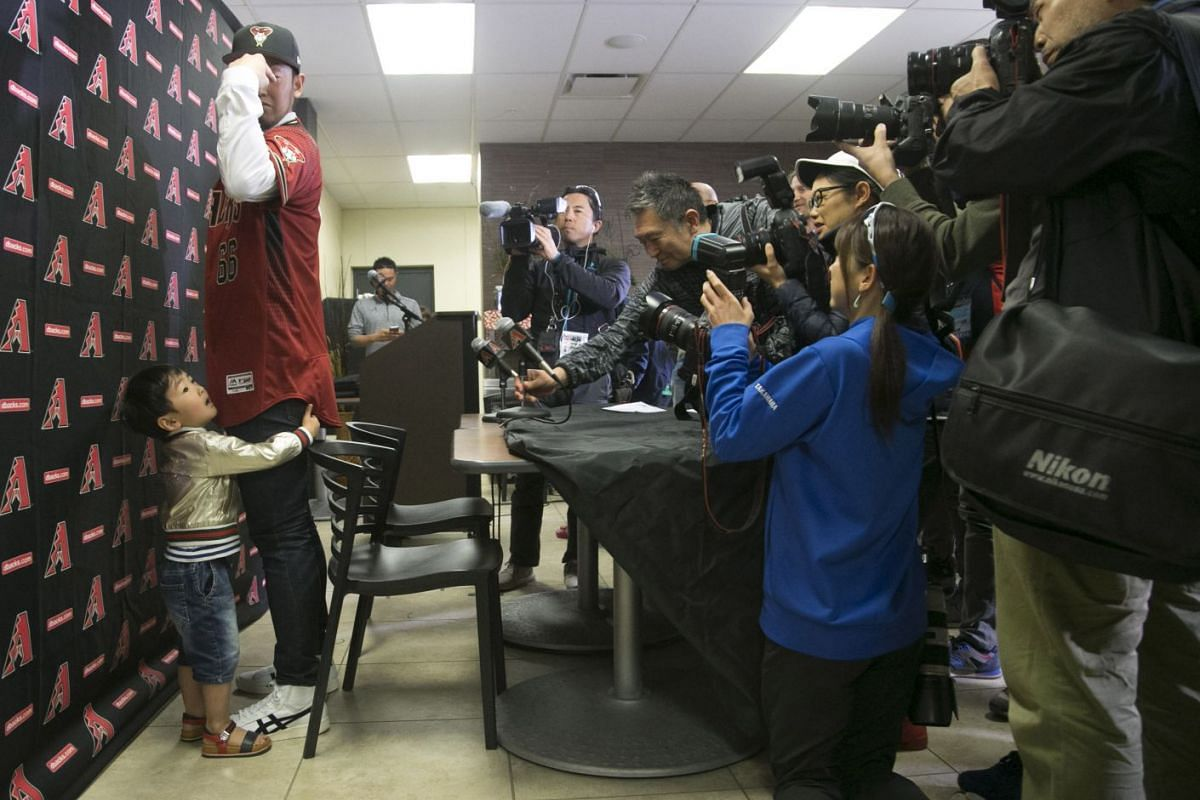 Newly-signed Japanese right-handed pitcher Yoshihisa Hirano (left) poses for photos for the media while wearing his Arizona Diamondbacks jersey as his three year old son Sena Hirano clings to his leg at an introductory press conference at Salt River