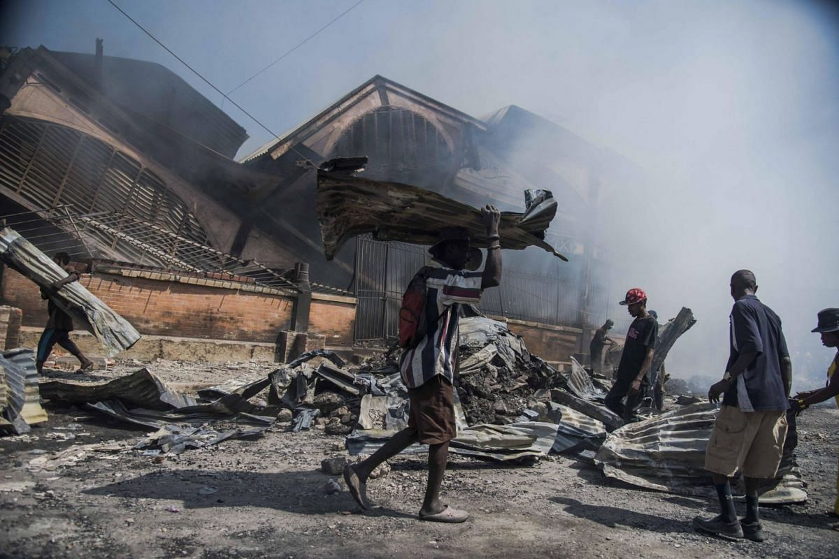 Men help to remove the debris at the scene of a devastating fire at the Hypolite market, in Port-au-Prince, Haiti, 13 February 2018. PHOTO: EPA-EFE