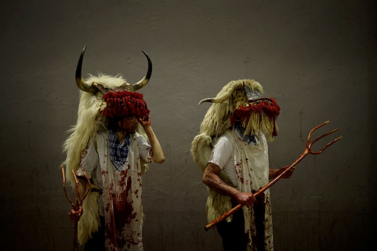 People dressed as Momotxorros, half bull, half man figures dressed in blood soaked sheepskins, take part in carnival celebrations in Alsasua, Spain, February 13, 2018. PHOTO: REUTERS