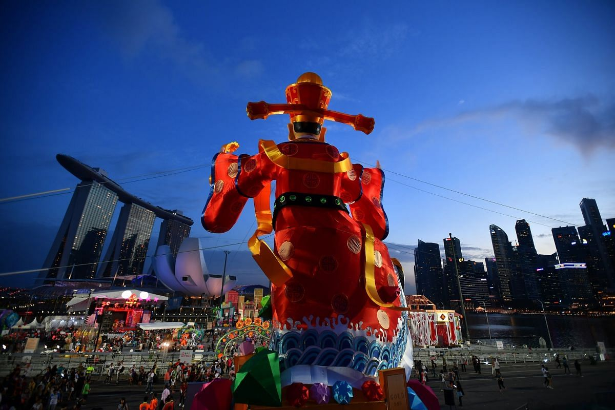 An 18m-tall statue of the God of Fortune is seen looking out over the Marina Bay skyline, during the opening ceremony of the River Hongbao 2018.