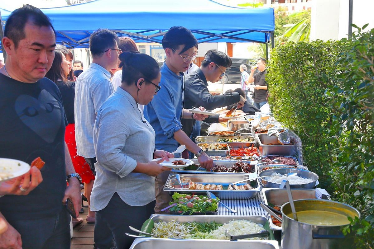 Invited guests take food from the buffet table.
