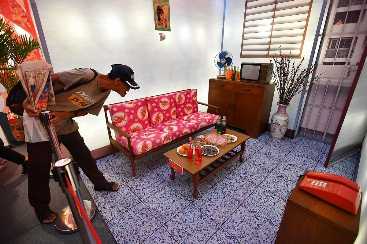 "A visitor examining the ""My Home, My New Year"" indoor exhibit at the River Hongbao. The display, the first indoor one, features full-sized displays of a kampung house, an old Housing Board flat and a modern home dining area as it traces the changing"