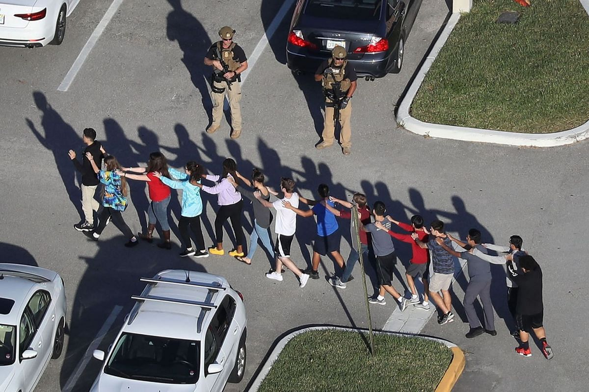 People are brought out of the Marjory Stoneman Douglas High School after a shooting at the school that reportedly killed and injured multiple people on February 14, 2018 in Parkland, Florida. PHOTO: GETTY IMAGES/AFP
