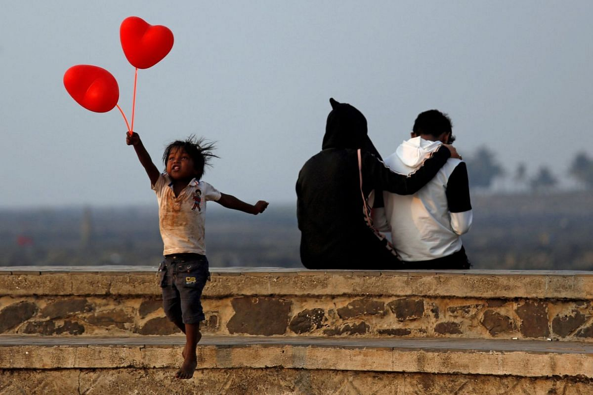 A child jumps from a promenade after attempting to sell heart-shaped balloons to a couple on Valentine's Day in Mumbai, India February 14, 2018. PHOTO: REUTERS