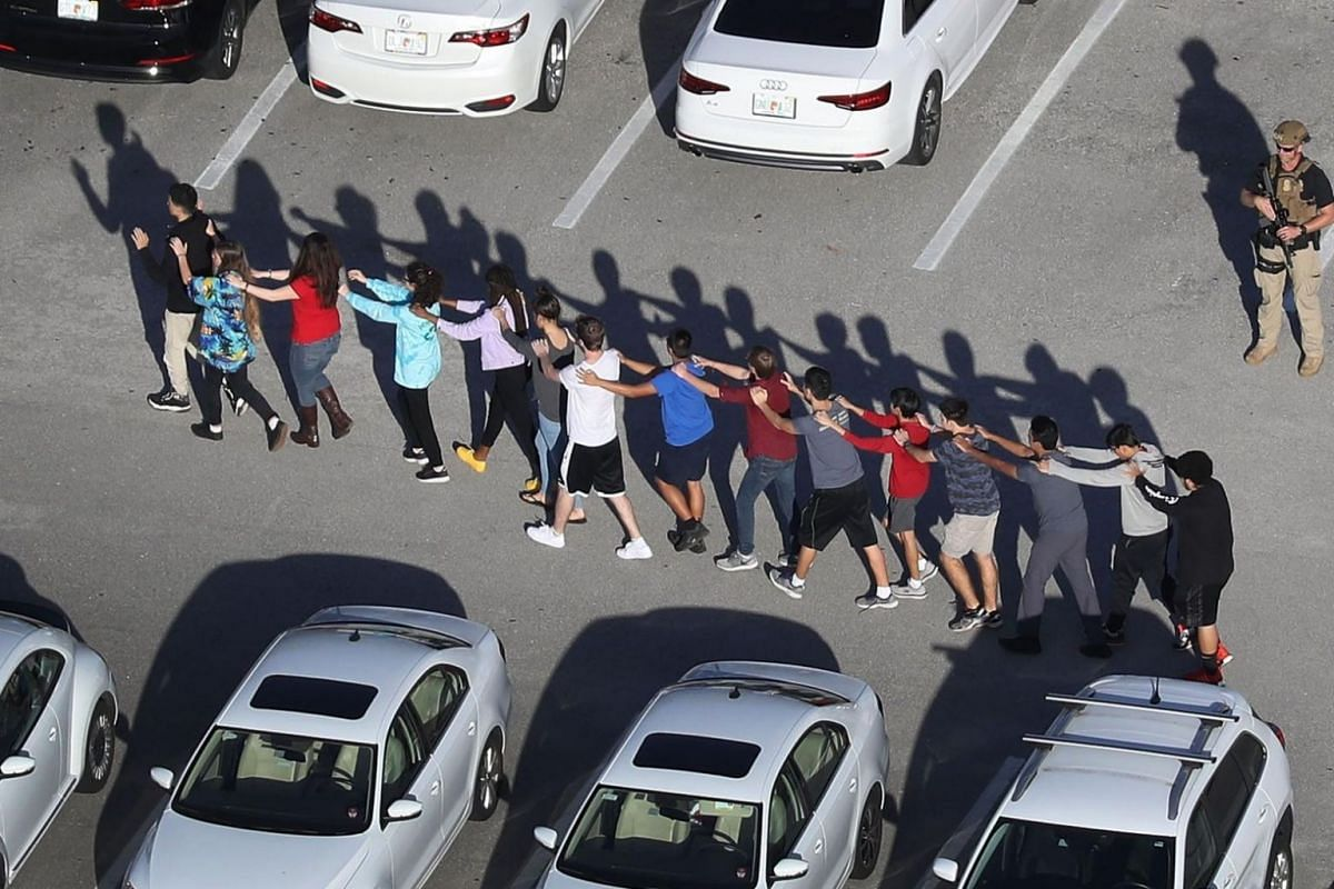 People being brought out of Marjory Stoneman Douglas High School in front of an armed official.