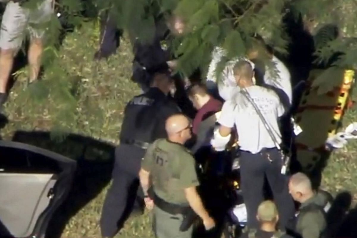 A man placed in handcuffs by police is loaded onto a stretcher near Marjory Stoneman Douglas High School.