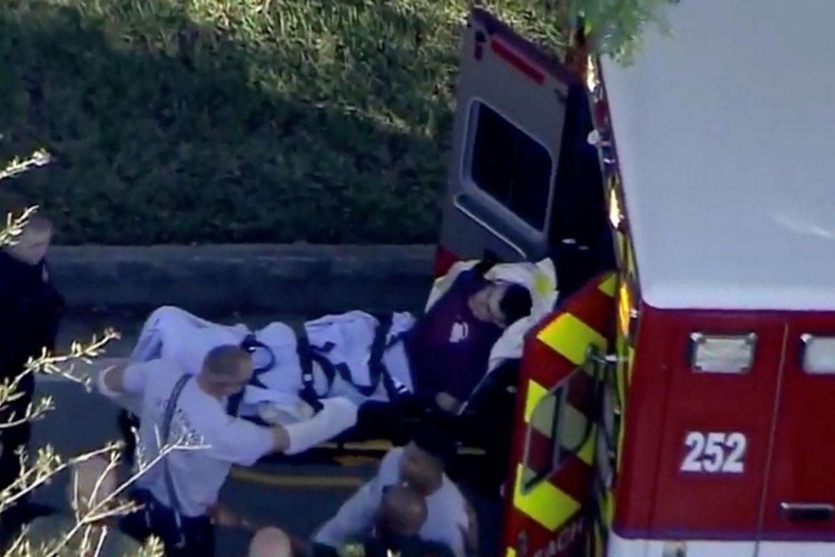 Paramedics loading the man who had been handcuffed onto an ambulance following the shooting.