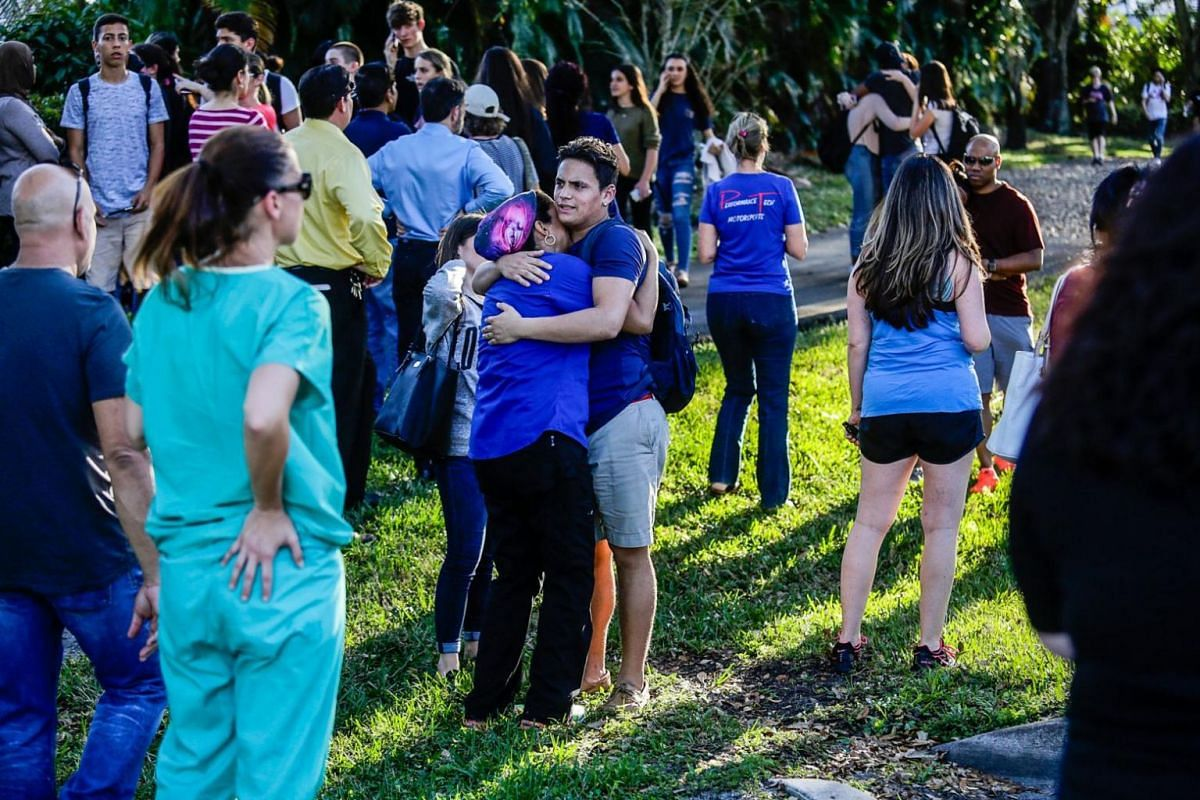 Students and parents embrace each other after the mass shooting that left at least 17 people dead.